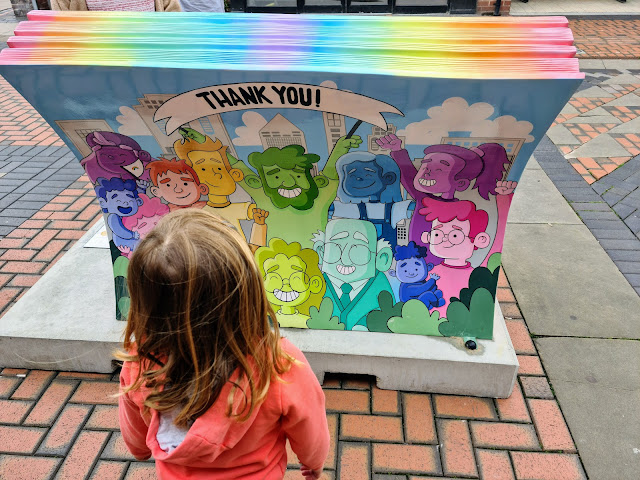 Image of a young girl admiring the Bassetlaw Nottinghamshire Book Benches. This book shows a variety of different aged people illustrated in different rainbow colours with the words 'thank you nhs' emblazoned on a banner at the top of the image.