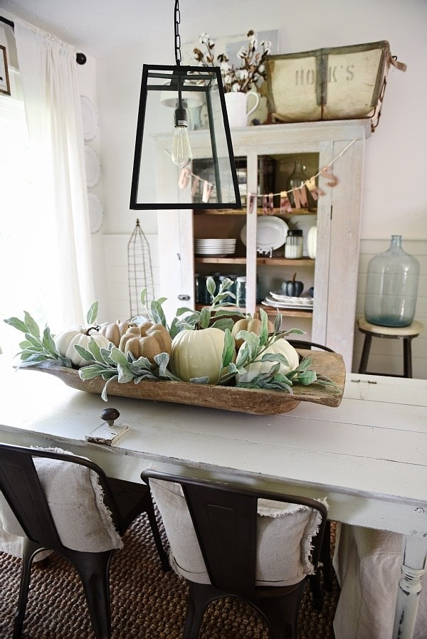 rustic farmhouse dining room decor for fall - how to decorate with a rustic antique bread bowl and pumpkins