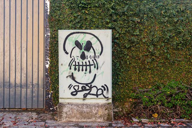Pichação, ou grafite, em uma caixa telefônica com a representação de uma caveira com o símbolo de radioatividade formando os orifícios dos olhos e do nariz