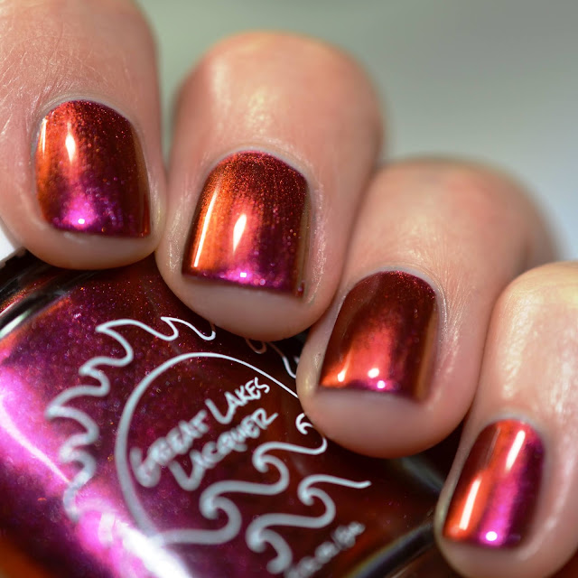 red multichrome nail polish that shifts through orange and magenta shown on the hands of a white person