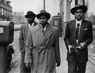 Three black men in suits and hats walking along a street in the 1940s