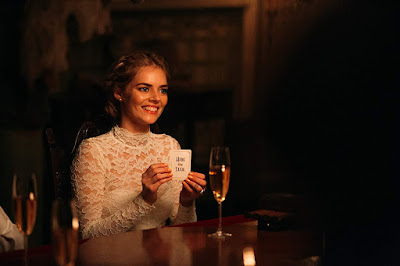 Movie still for the 2019 thriller Ready or Not where Samara Weaving's character Grace holds up a Hide and Seek playing card and seals her fate