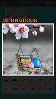 небольшая миниатюра с подушками на качелях под цветущими цветами