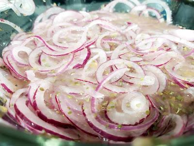 Cebolla marinando, la carne de la cebolla es blanca y el borde morado