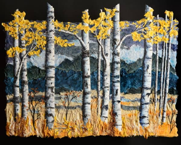 textured paper collage of birch trees in autumn with mountains in background
