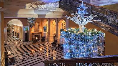 A blue-decorated upside-down Christmas tree in the lobby of an elegant hotel with black and white flooring