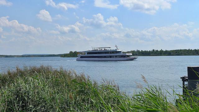Sommerausflug an den Markkleeberger See - Schilfrohr im Vordergrund, Personenschiff auf dem See, blauer Himmel