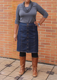 A denim skirt made from the DIBY Club Anna Skirt sewing pattern, modeled with boots and a turtleneck against a brick wall.