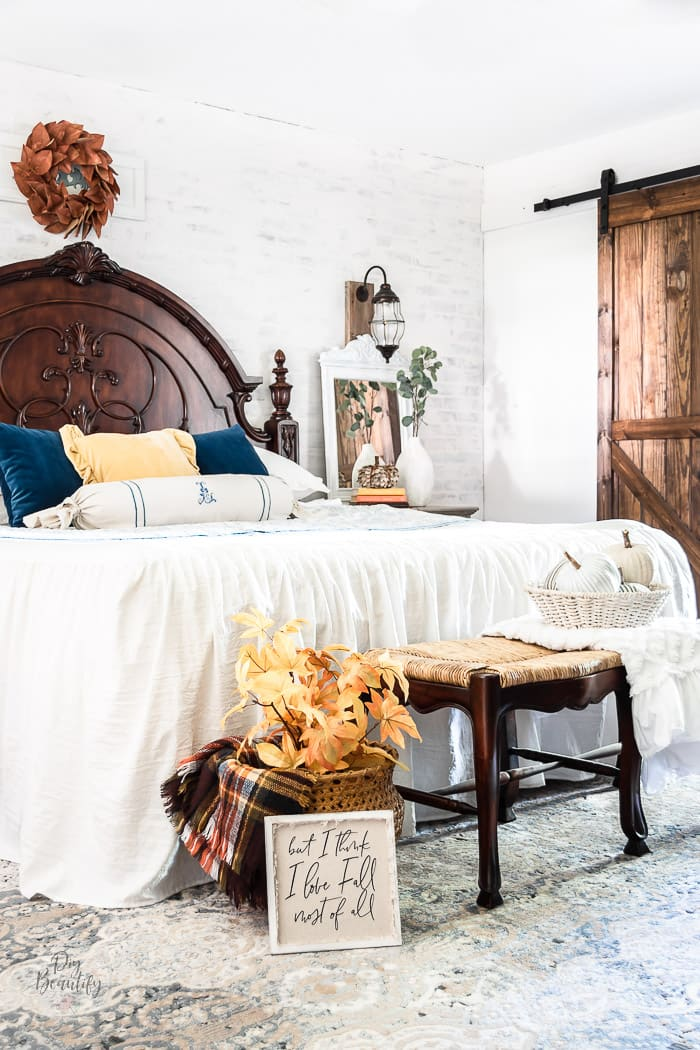 tall dark headboard with copper magnolia wreath, blue and white linens, yellow and blue pillows, white brick wall, barn door and fall leaves