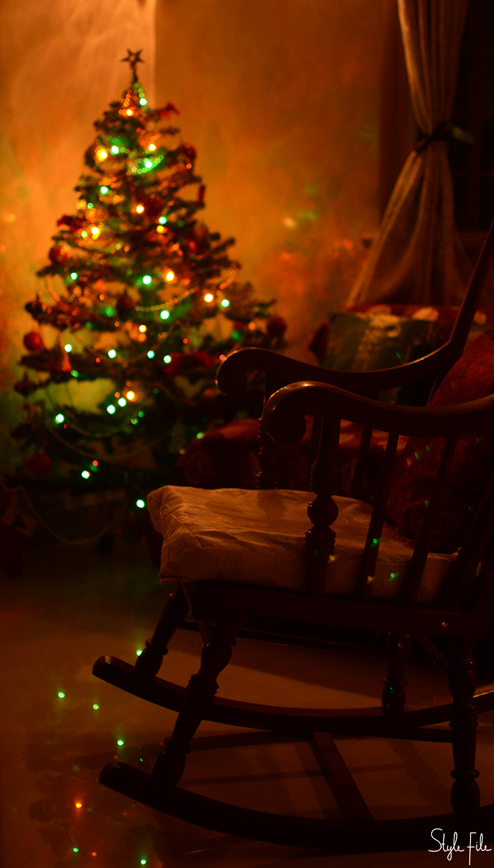 Image of a decorated Christmas tree with lights and a star along with a rocking chair at the side of it