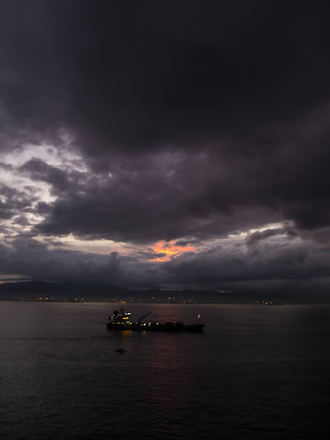 Dark clouds and last light of day in the port of Gibraltar with a boat in the centre.