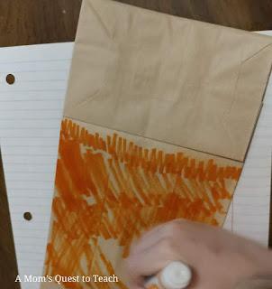 coloring bottom of brown paper bag orange with marker