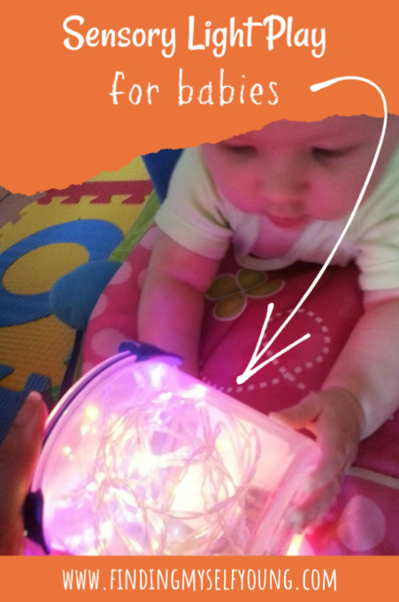 Baby playing with christmas lights in a plastic container.