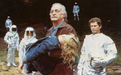 """Movie review for """"Firestarter"""" and movie still where George C. Scott carries an unconscious Drew Barrymore away from men in silver hazard suits"""