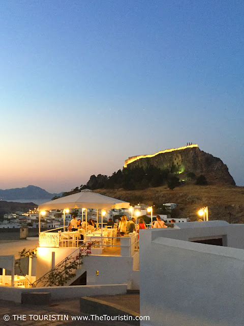 A crowd of people in a white rooftop restaurant at sunset in front of a castle on top of a mountain.