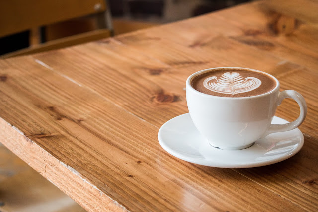 A cup of coffee sat on a wooden table