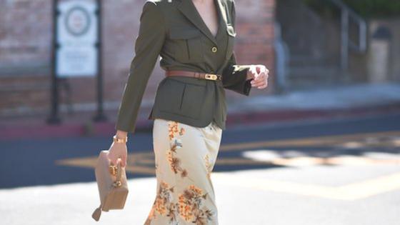 Imagem ilustrativa ao tema. Look com saia branca com padrão floral, casaco verde tropa com cinto camel por fora do casaco