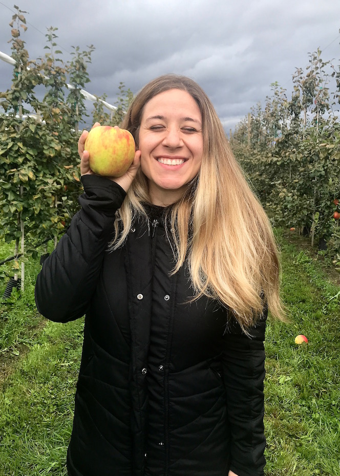 holding an apple in the apple orchard