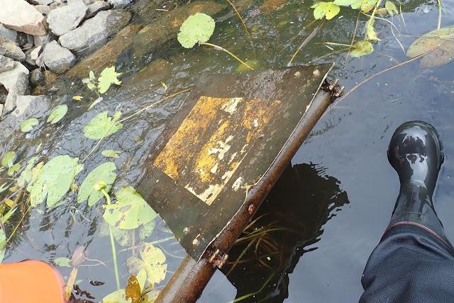 Metallinen opastustaulu pinnalla, joja on juuri nostettu meren pohjasta. Taustalla lumpeen lehtiä.