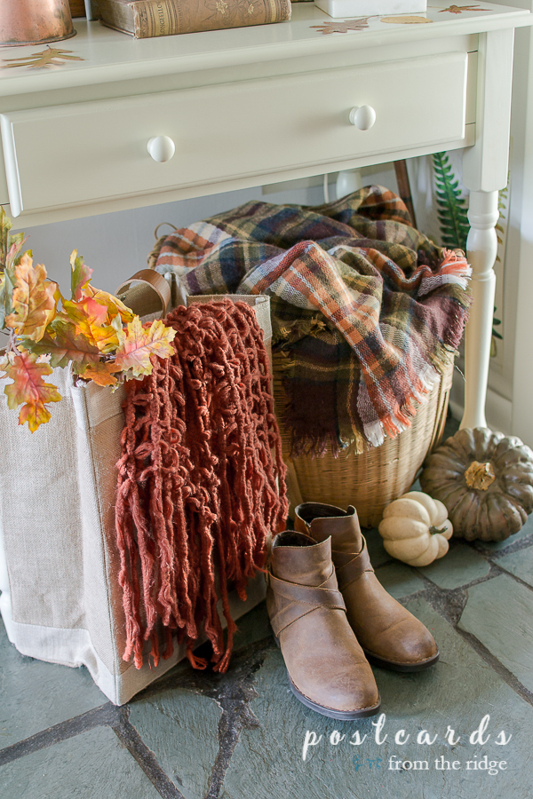 boots, bag with rust scarf, faux pumpkins on slate floor