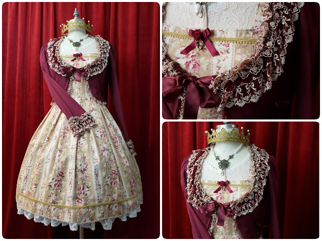 First Coordinate of the dress with a dark red cardigan layered on top and a gold crown on mannequin