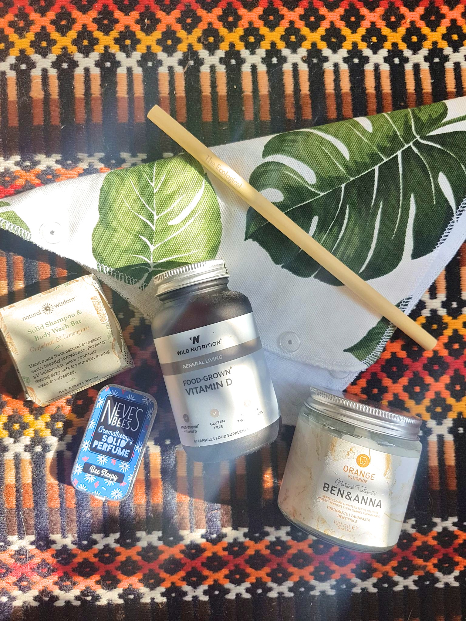 Zero Waste products including bamboo straw, solid perfume, reusable towels, plastic free toothpaste, vegan vitamins, and eco friendly shampoo and body wash
