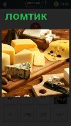 На доске порезан ломтиками разный сыр