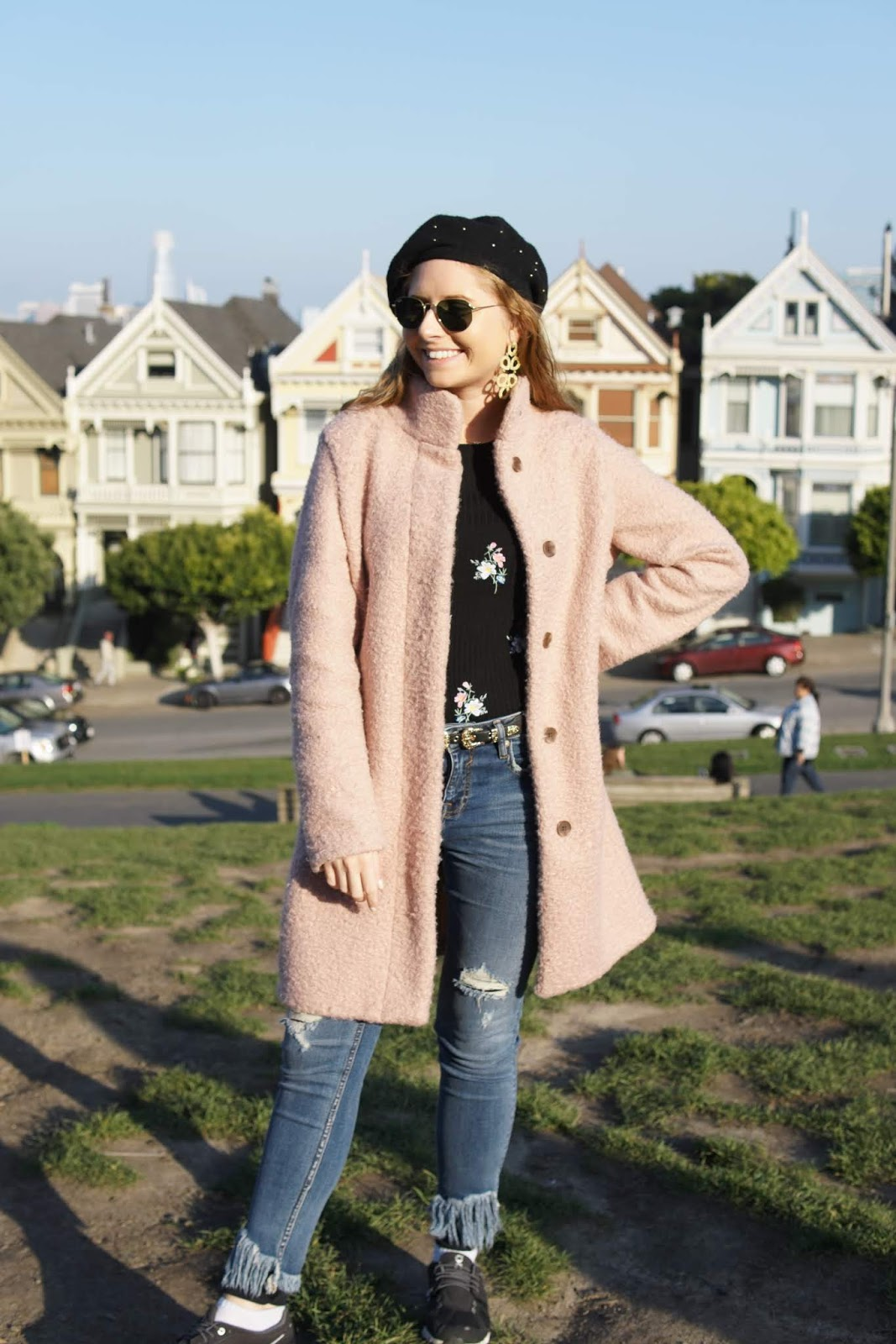 tampa blogger amanda burrows stands in front of the painted ladies in san francisco, california. she is wearing a pink boucle coat from old navy with a floral sweater and pair of dark jeans.