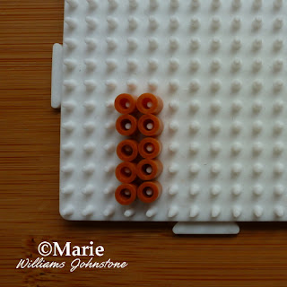 brown beads on white pegboard