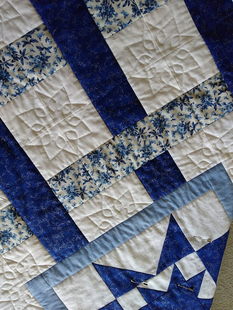 Detail of quilted bloom motif on blue and white quilt