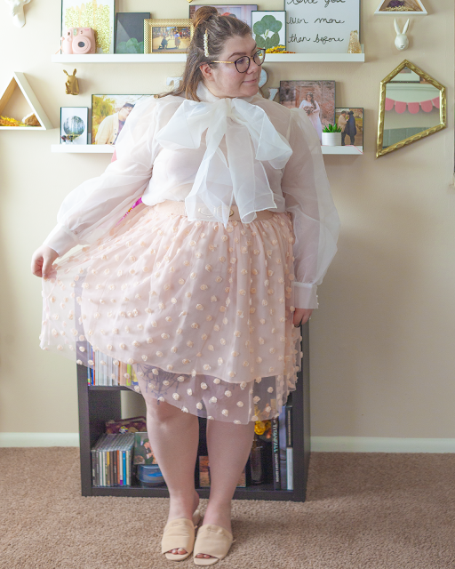 An outfit consisting of a sheer long sleeve blouse with an attached bow tucked into a pastel pink midi skirt with a sheer overlay with rosettes attached to it and pastel pink slide sandals.