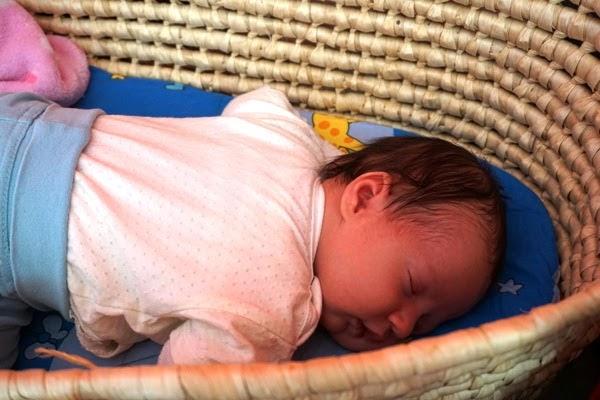 noworodek śpi na brzuszku w koszu mojżesza