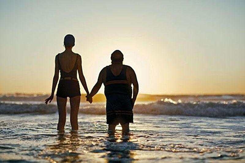 пара, смотрящая на закат солнца на пляже