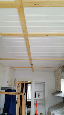 Beadboard installed on kitchen ceiling with lath to cover the seams