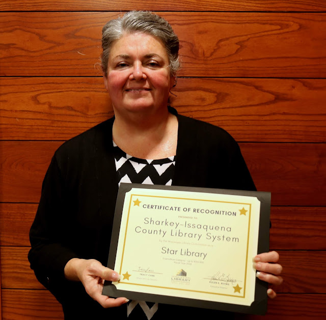 smiling woman holds a certificate of recognition for sharkey issaquena county library system