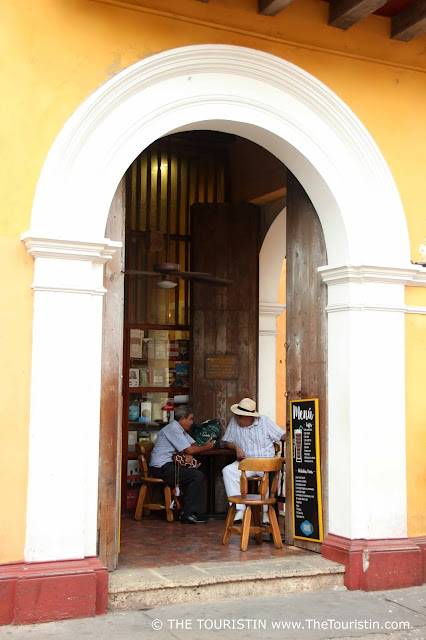 A vaulted entrance of a yellow painted house with two chatting gentleman sitting on the porch.