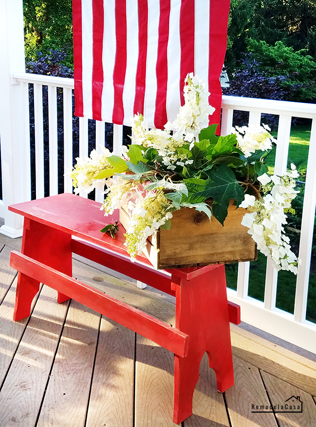 red bench with wooden box full of white blooms