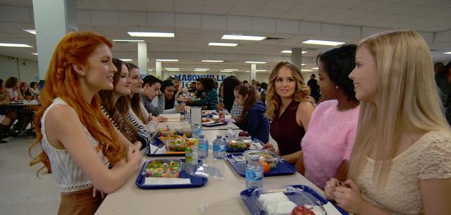 6 chicas prototipo populares tomando ensalada al fondo se ven otros estudiantes con diversos platos y bebidas