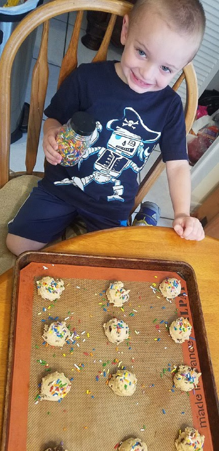 Antonio is helping grandma bake these best ever peanut butter chocolate chip cookies and pouring sprinkles on them