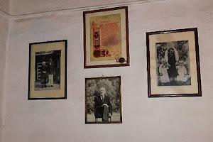 Obrazy i fotografie wiszące na ścianach izby.