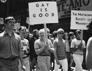 """Protesters carrying a """"Gay is Good"""" placard"""