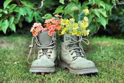Liberdade feminina. Par de botas usados como vaso de flores sobre a relva.