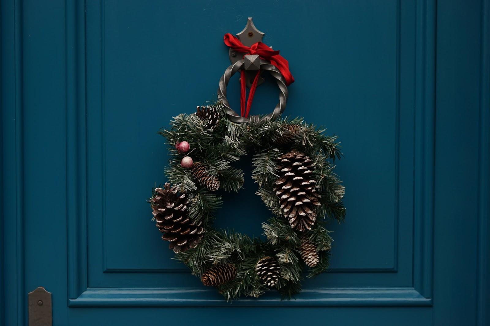松毬が付いたクリスマスリースがかかった深い青の扉