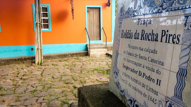 Placa com texto e casa laranja ao fundo