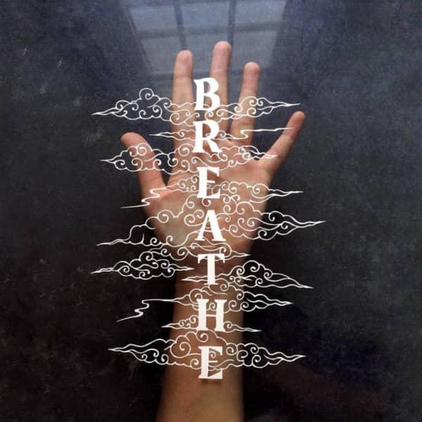 papercutting van woord ademen omgeven door papercut en weergegeven op open palm van handscrolls