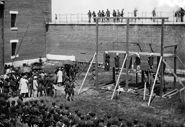The hanging hooded bodies of the four conspirators, Mary Surratt, Lewis Powell (Payne), David Herold, and George Atzerodt, executed on July 7, 1865 at Fort McNair in Washington, District of Columbia, All four had been convicted of taking part in the conspiracy to assassinate Abraham Lincoln.