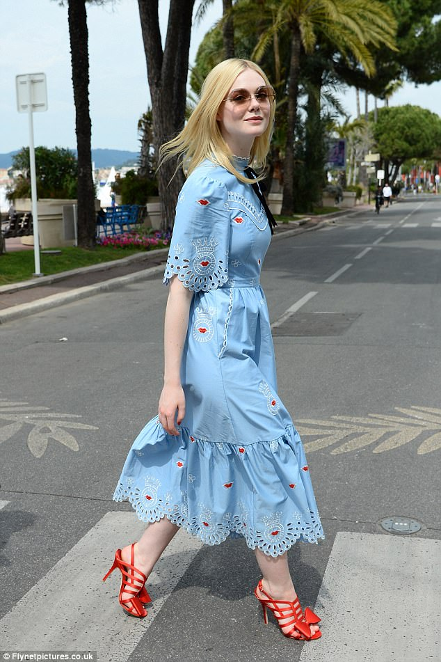 Elle Fanning stuns in a quirky blue frock with eye-catching red heels as she steps out during the Cannes Film Festival