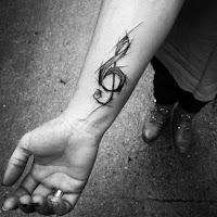 tatuaje clave de sol en el antebrazo