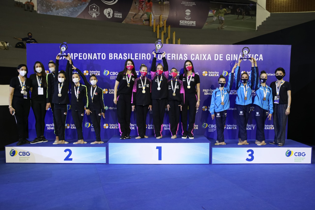 Atletas e técnicas no pódio da competição por equipes. As atletas estão com medalhas no pescoço e levantando um troféu