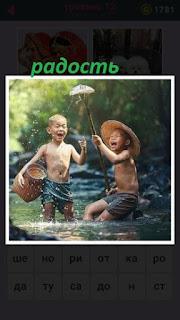 двое мальчиков в речке поймали рыбу острогой и в радости подняли вверх